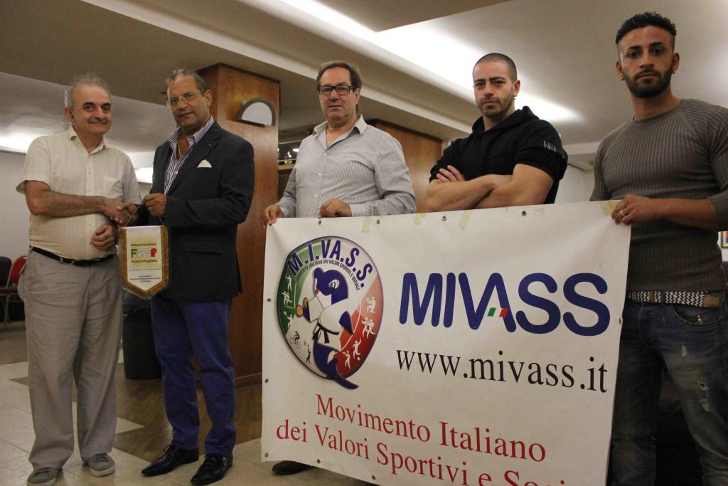 IL Segretario FISP Sergio Pagano porge il gagliardetto al Presidente Onorario MIVASS Lorenzo Lomanno.
